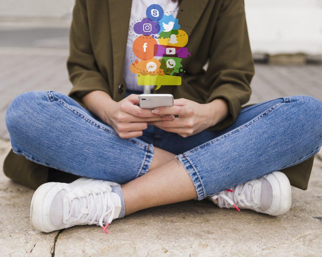 Lady sitting crossed leg on her phone scrolling through Social Media