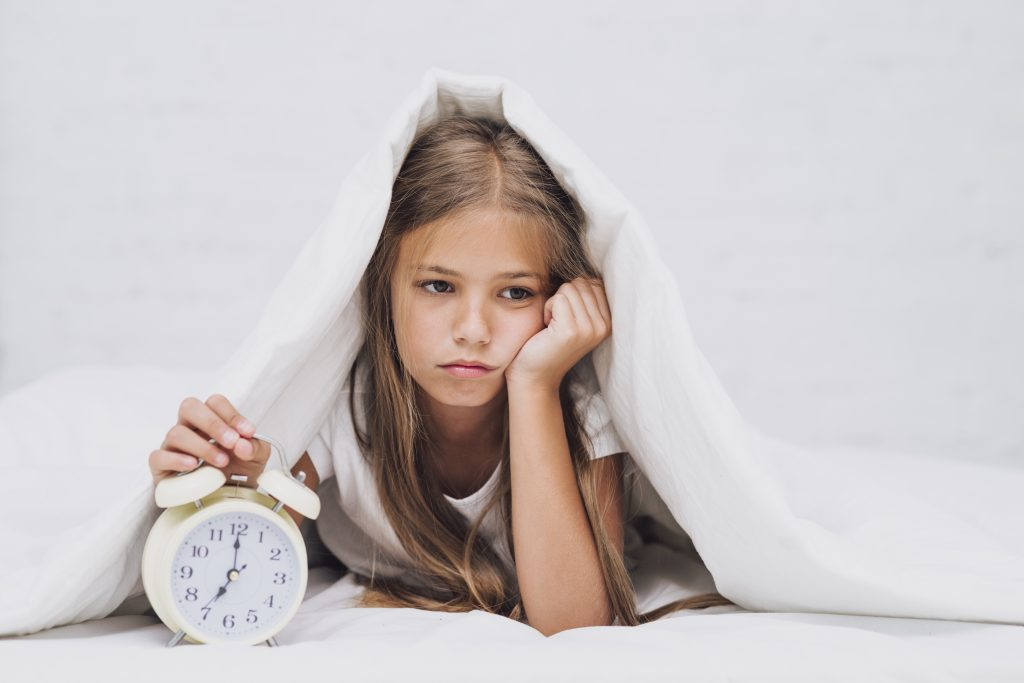 Girl lying in bed with a clock looking sad