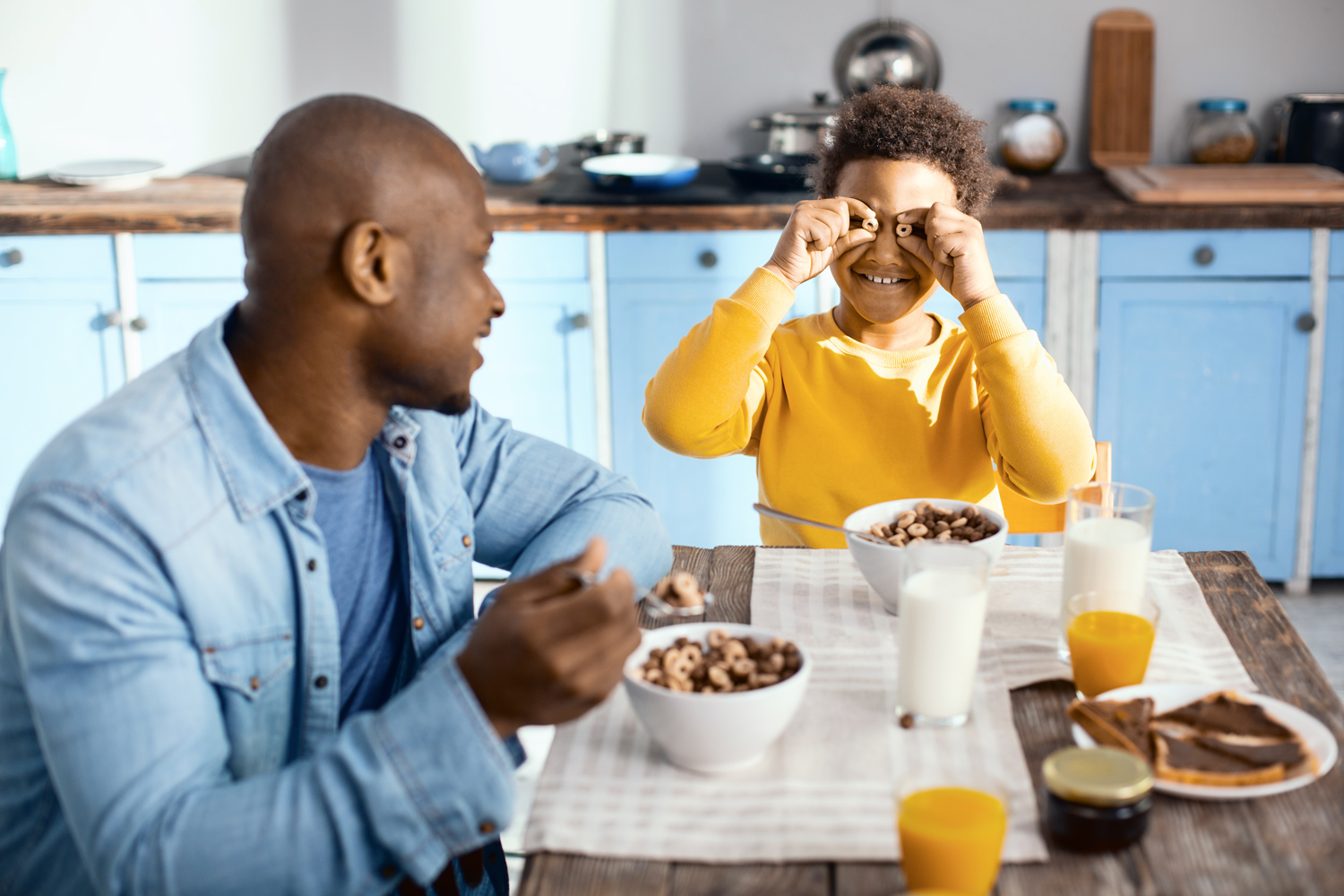 Great mood. Charming pre-teen bot sitting at the table and holding two cereal rings near his eyes, joking with his father while having breakfast