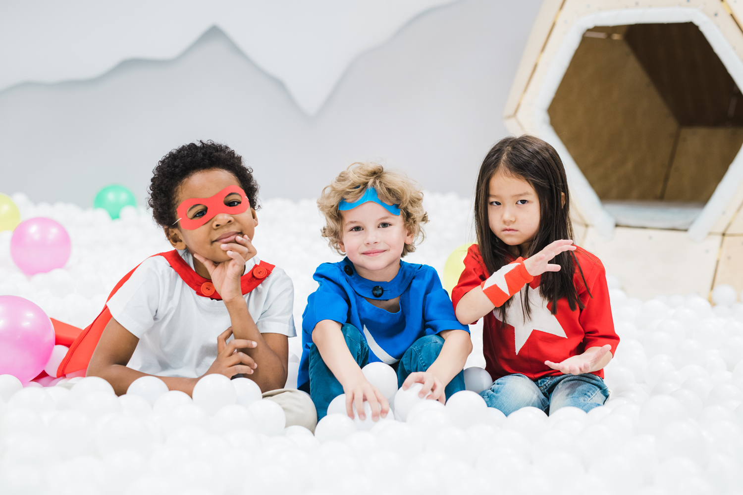Transferring foster agency for different foster parents and children - Group of adorable little intercultural friends in costumes sitting in balloons