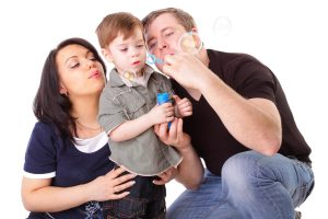 Happy family having fun. Man, woman and child blow bubbles. Series