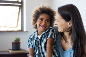 transferring foster agency and it's a son and mother. Close up face of latin woman playing with her african son. Happy young son feeling loved by mother. Portrait of a lovely mom and cute little black boy looking up at home. Adoption and family concept.