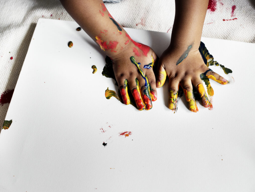 Child painting and using his hands as prints