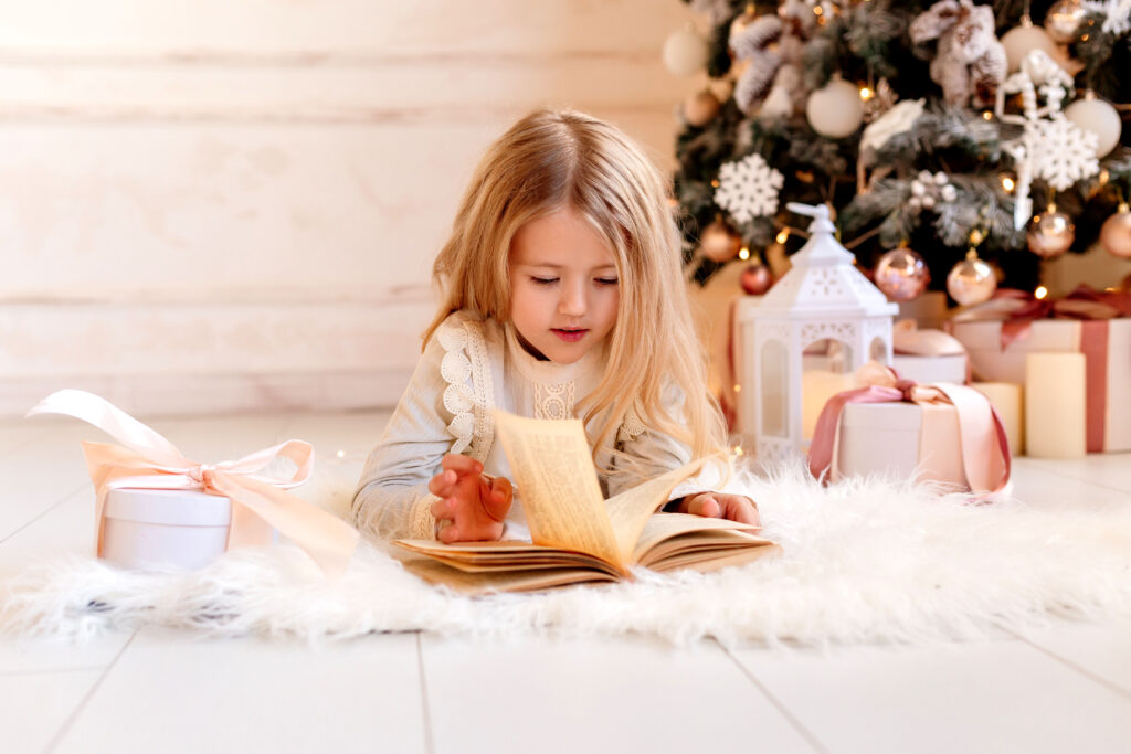 Cute little blonde girl reads a book at home near the Christmas tree