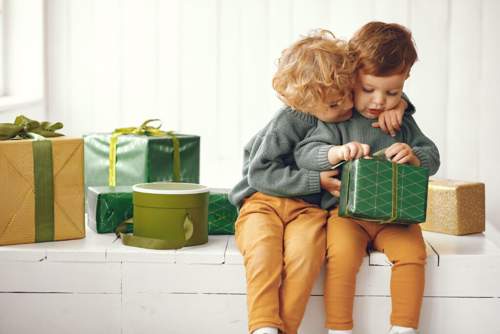 Cute little boys in a studio. Children sitting by the christmas gifts. Kid in a gray sweater.