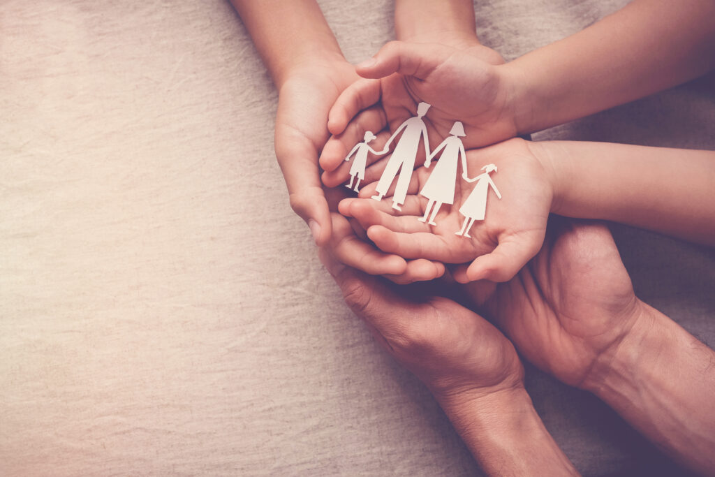 Adult and children hands holding paper family cutout, family home, foster care, homeless support for foster carers concept