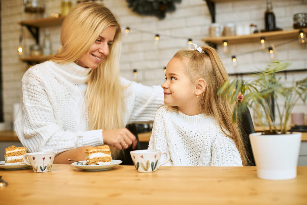 Cozy image of happy young mother with long blonde hair posing in kitchen with her adorable daughter, sitting at table, having tea and eating cake, looking at each other and smiling, talking