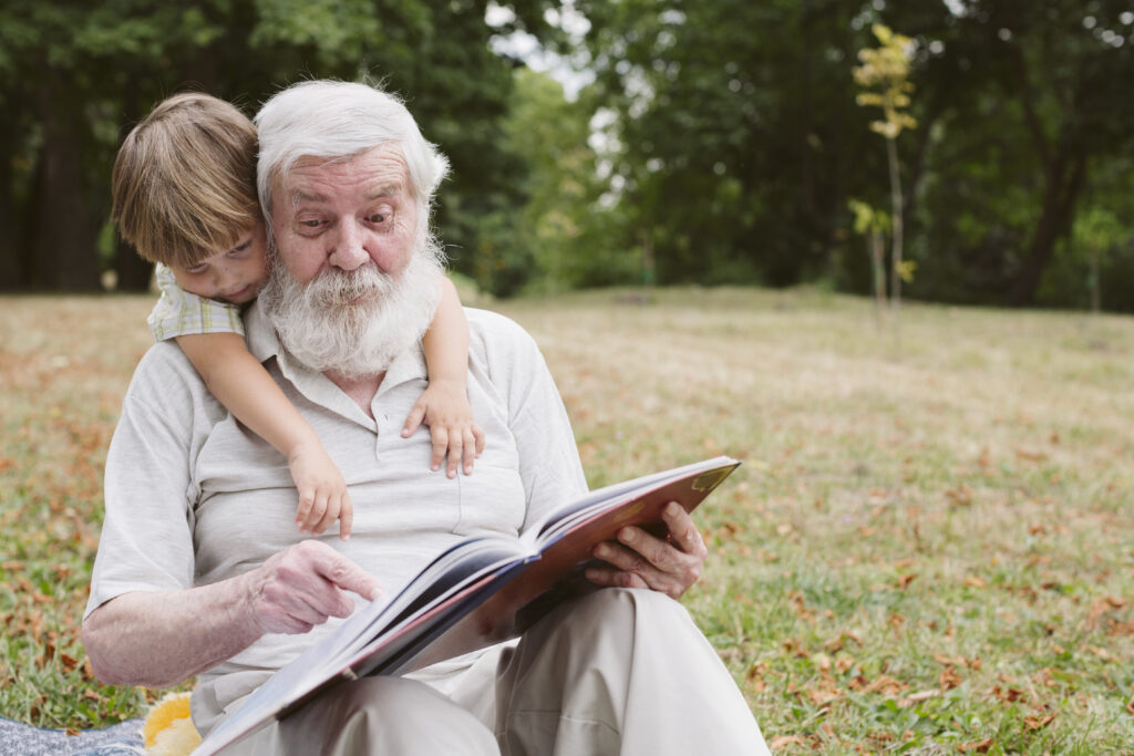grandpa and foster children reading together in the garden